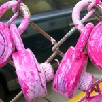 Pink padlocks on chain-link fence